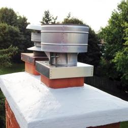 A raincap for gas fastened to a flue tile cover.